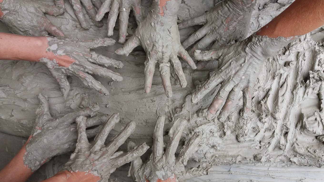 multiple hands covered in mud