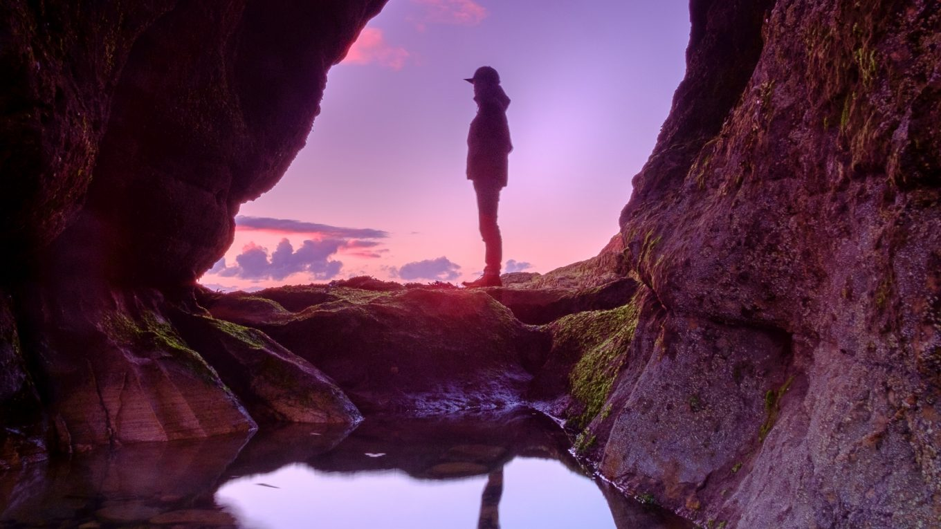 person standing in cave entrance with reflection in pool of water