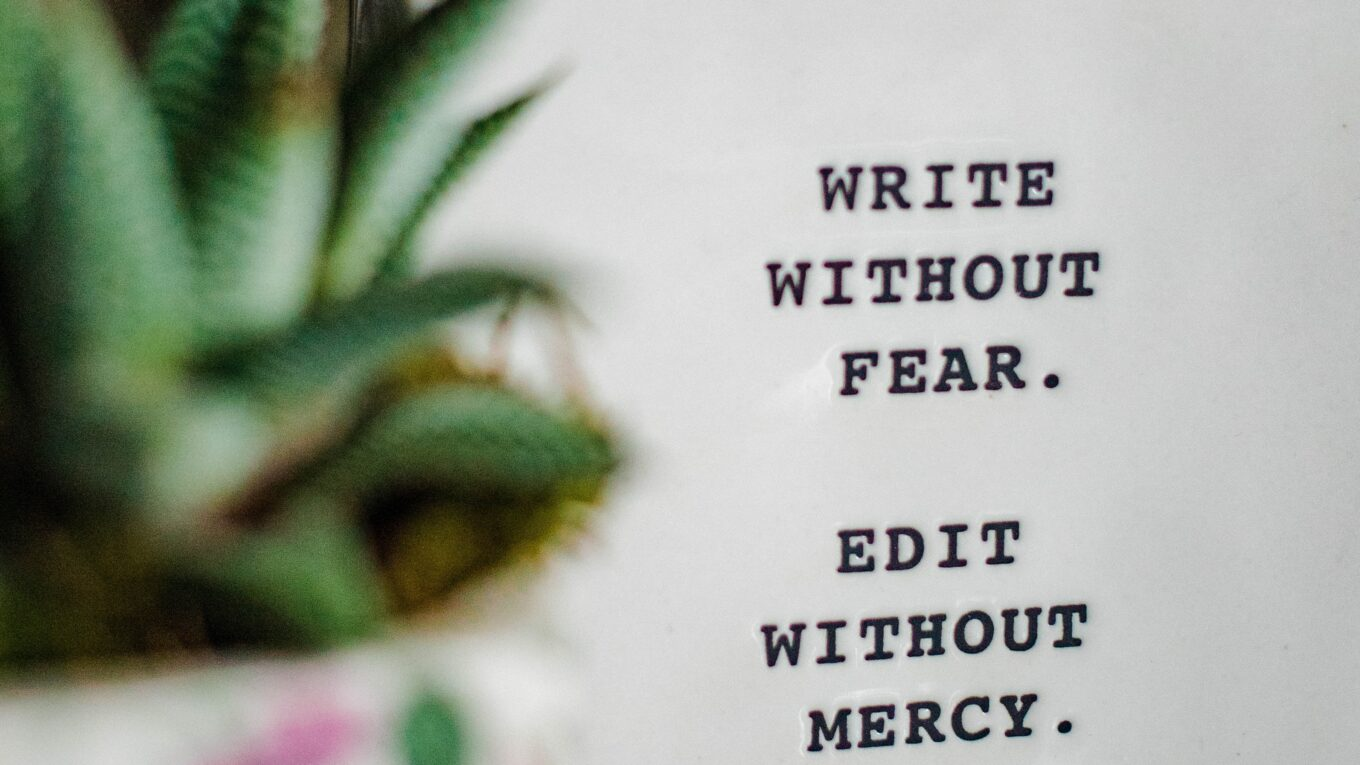 """text saying """"write without fear. Edit without mercy"""" imposed beside an out of focus plant in a pot"""